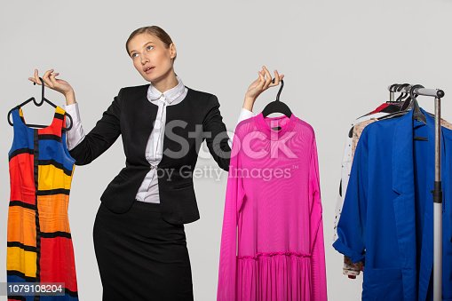 672064598istockphoto girl in an office suit holds dresses and thinks 1079108204