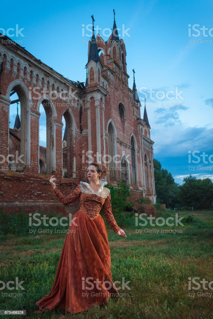 Girl in an old dress of the Shakespeare era (1500-1600) posing near an abandoned castle stock photo