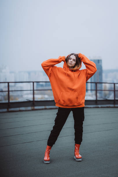 Girl in an orange jacket poses on the roof of a building in the city center stock photo