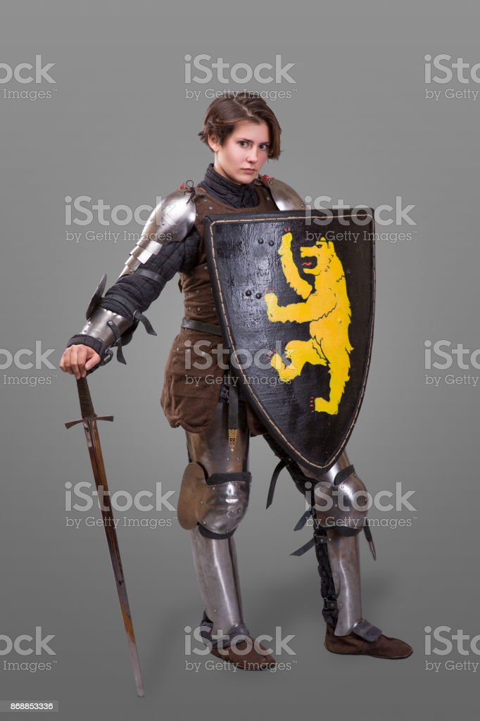Girl in armor with a sword knight wuth shield over grey background stock photo