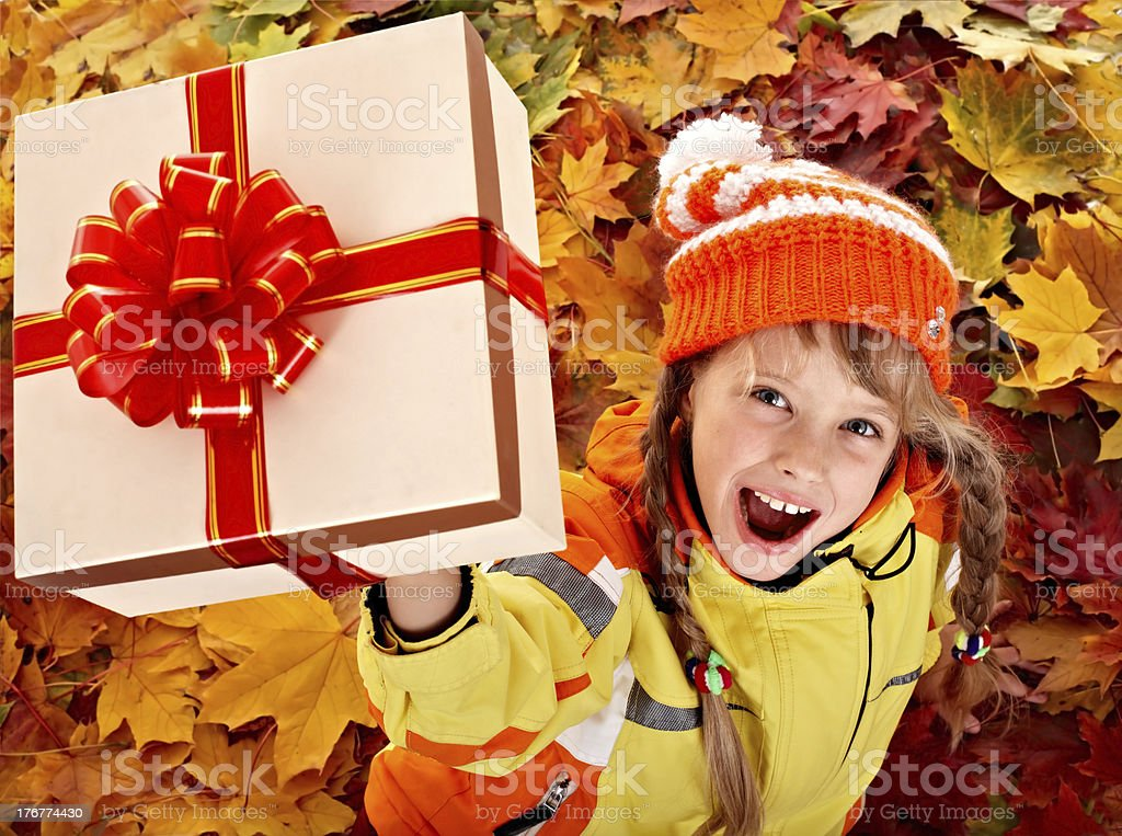 Girl in autumn orange hat on leaf and gift box. royalty-free stock photo