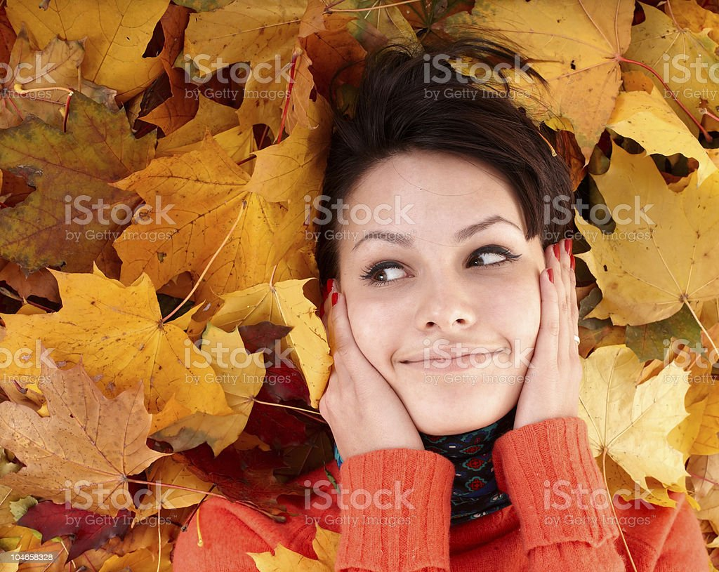 Girl in autumn orange sweater on leaf group. royalty-free stock photo