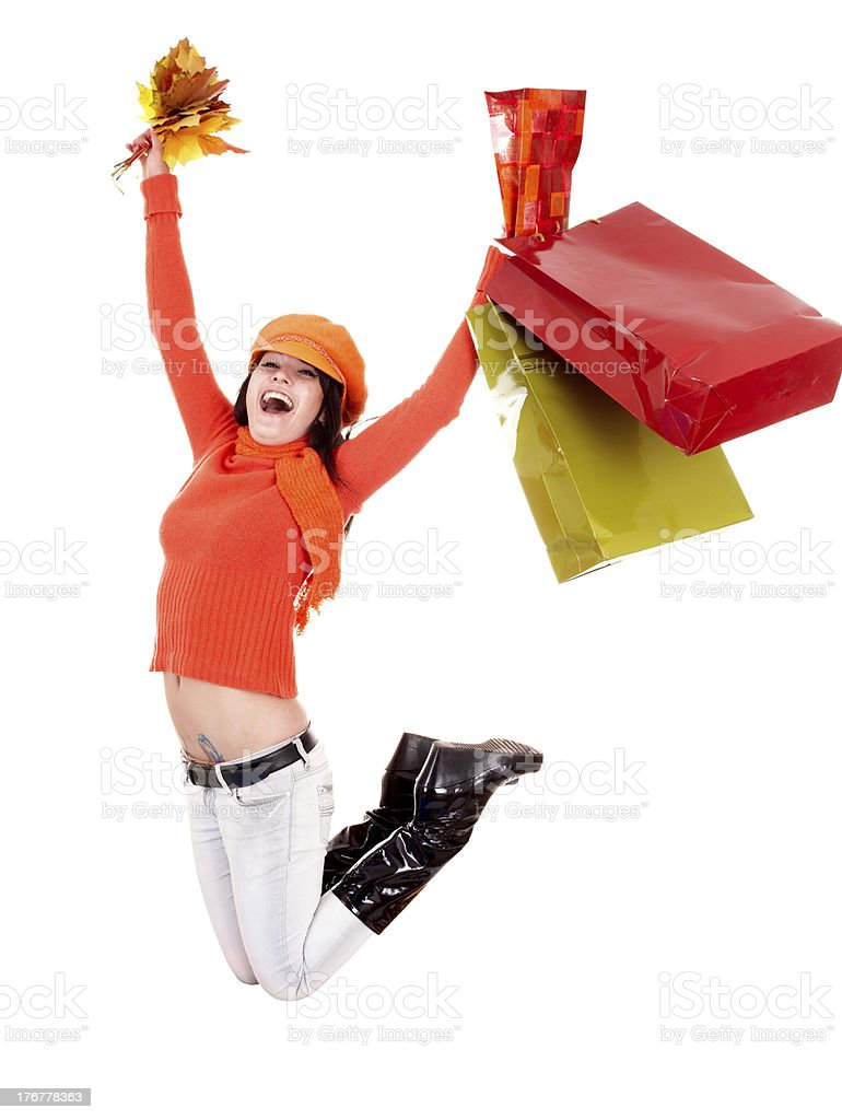 Girl in autumn orange sweater with leaf, shopping bag jump. royalty-free stock photo