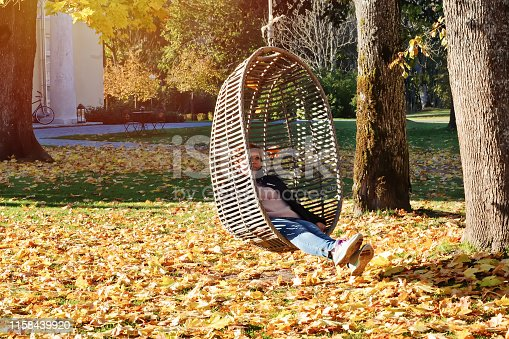 Millennial girl in autumn park swinging on hanging rattan egg-shaped chair outdoor in the midst of fallen leaves
