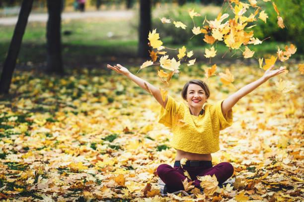 menina no outono senta-se na grama e alegremente projeta as folhas amarelas. estilo de vida. - setembro amarelo - fotografias e filmes do acervo