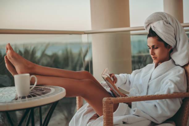 girl in bathrobe reading a book on a balcony - accappatoio foto e immagini stock