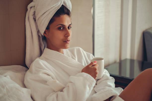 Chica en bata de baño con la toalla en su cabello tomando café - foto de stock