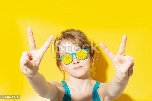 istock Girl in beach outfit showing two fingers 948975526