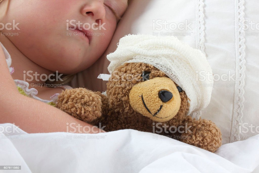 Girl in bed cuddling a teddy with bandage stock photo
