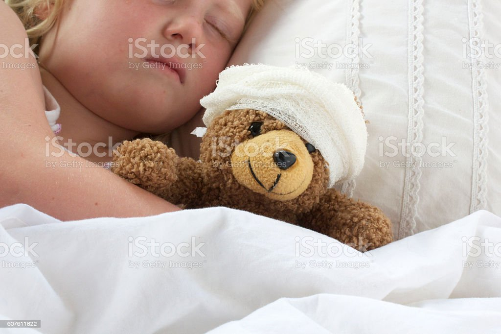 Girl in bed cuddling a teddy with bandage - foto de stock