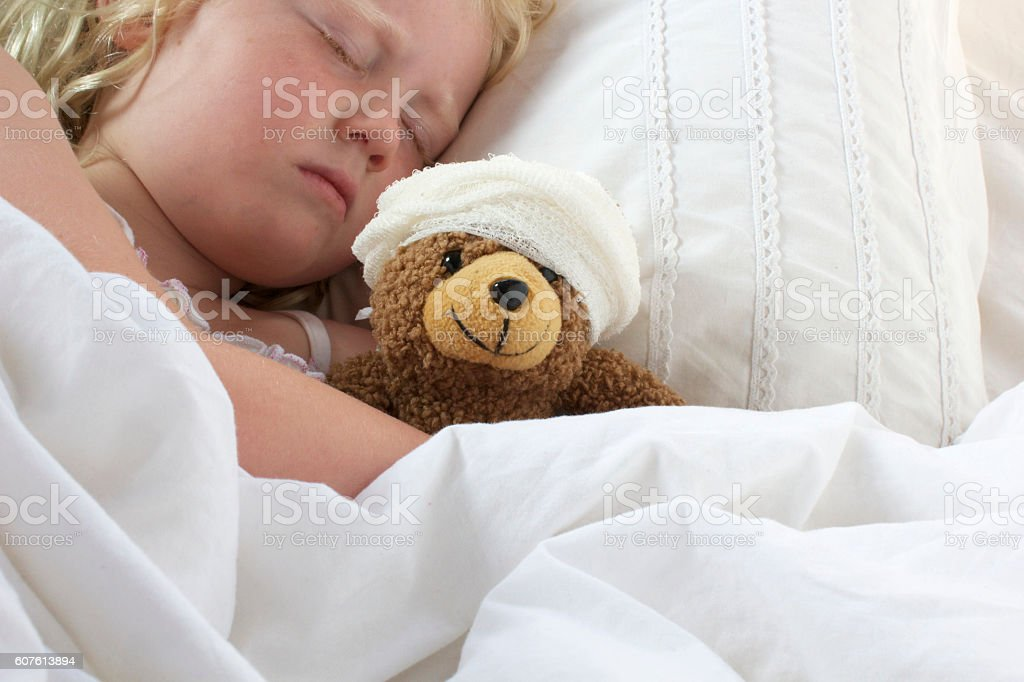 Girl in bed cuddling teddy with bandage - foto de stock