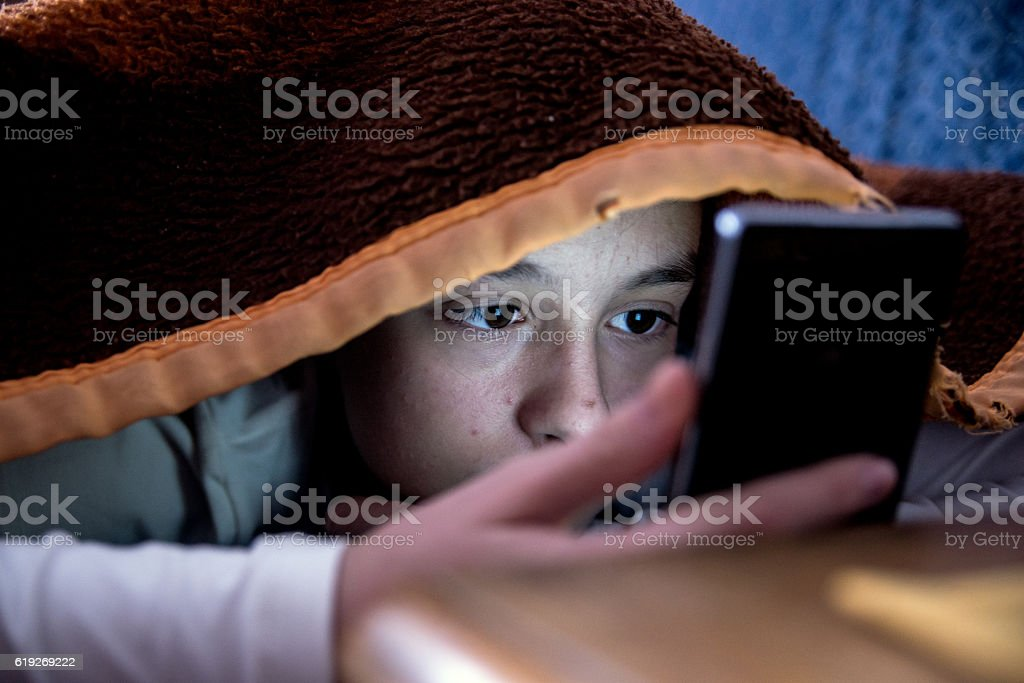 girl in bed texting on smartphone ストックフォト