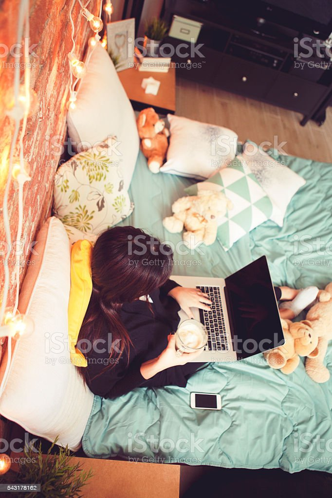 Girl in bed with lap top stock photo