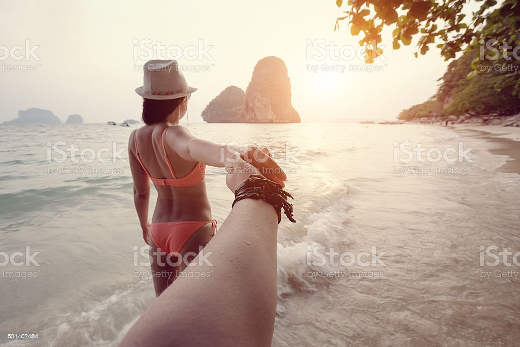 Girl in bikini holding a hand Man on the beach stock photo