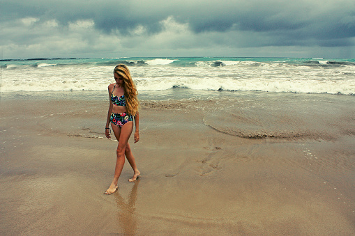 girl in bikini on beach at stormy sea, Galapagos island