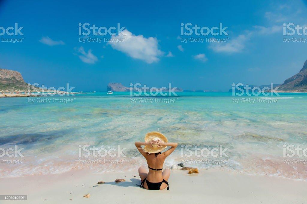 girl in black bikini and with hat on Balos beach stock photo