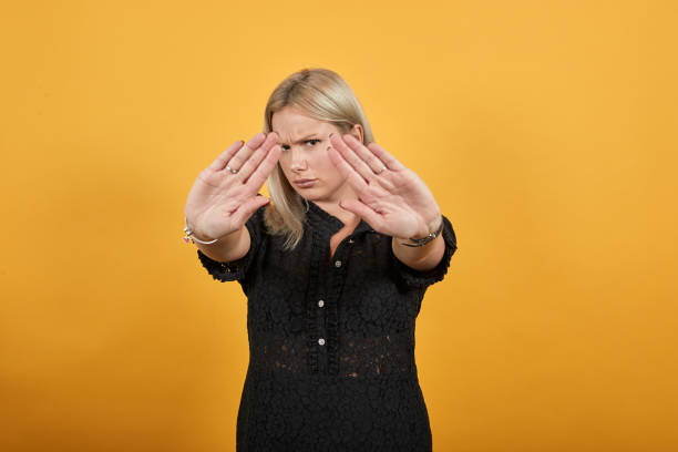 girl in black dress irritated angry woman stops with her hands shows palms Beautiful blonde girl in black dress on yellow background irritated angry woman stops with her hands shows palms alas stock pictures, royalty-free photos & images