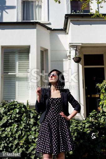 istock Girl in black dress with polka dots and sunglasses 514853442