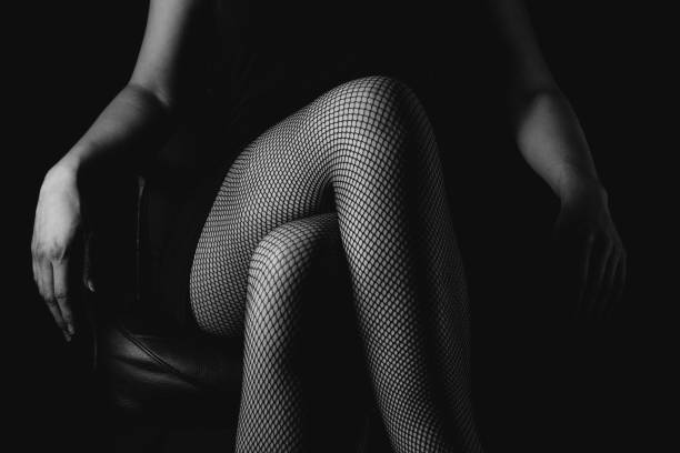 girl in black fishnet stockings against dark background. sexy woman in stockings sitting on chair. strict woman domination bdsm concept. - nylon texture stock pictures, royalty-free photos & images