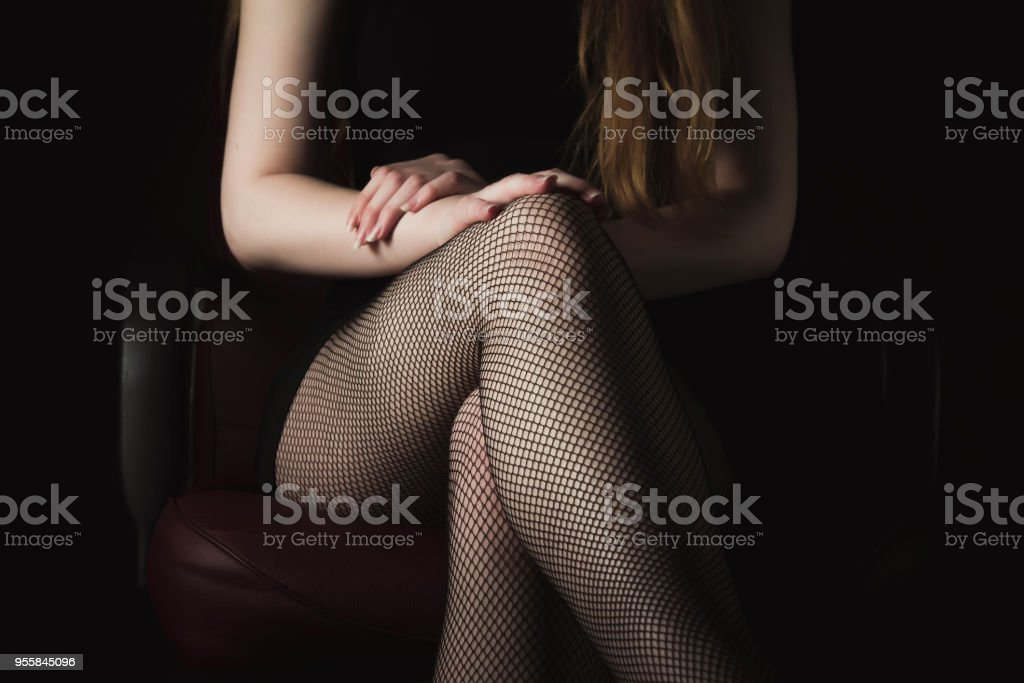 Girl in black fishnet stockings against dark background. Sexy woman in stockings sitting on chair. Strict woman domination bdsm concept. stock photo
