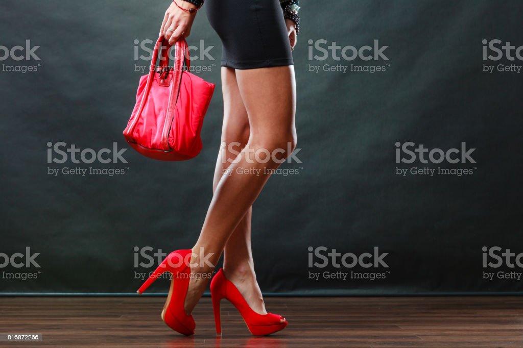 f3218585400013 Meisje in zwarte korte jurk rood puntige schoenen houdt handtas royalty  free stockfoto