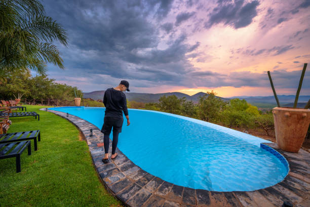 Girl in black standing beside a swimming pool in a luxury resort at sunset stock photo