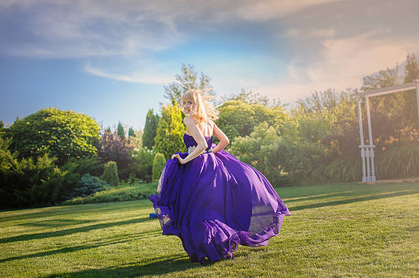 girl in blowing dress outdoors - abendkleid lang blau stock-fotos und bilder