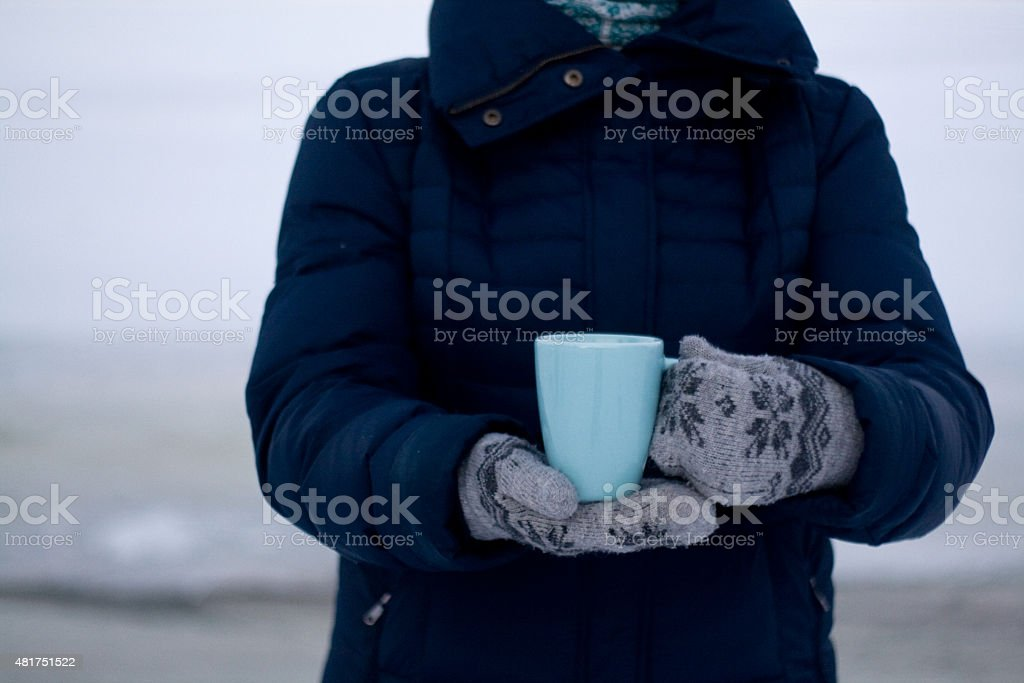 Girl in blue down jacket holding a blue cup stock photo