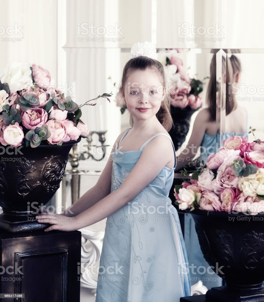 Girl in blue dress is standing in a large room with flowers royalty-free stock photo