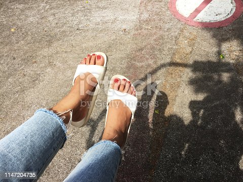 955947208 istock photo Girl in Blue Jeans and White Shoes Isolated from Top View. Woman Wearing White Sandals of Accessory on Concrete Background Great For Any Use. 1147204735