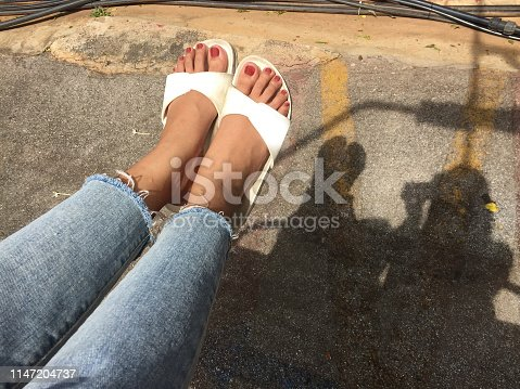 955947208 istock photo Girl in Blue Jeans and White Shoes Isolated from Top View. Woman Wearing White Sandals of Accessory on Concrete Background Great For Any Use. 1147204737