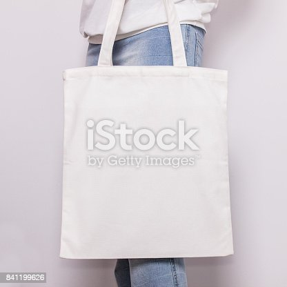 istock Girl in blue jeans holds blank cotton eco tote bag, design mockup. Handmade shopping bag for girls 841199626