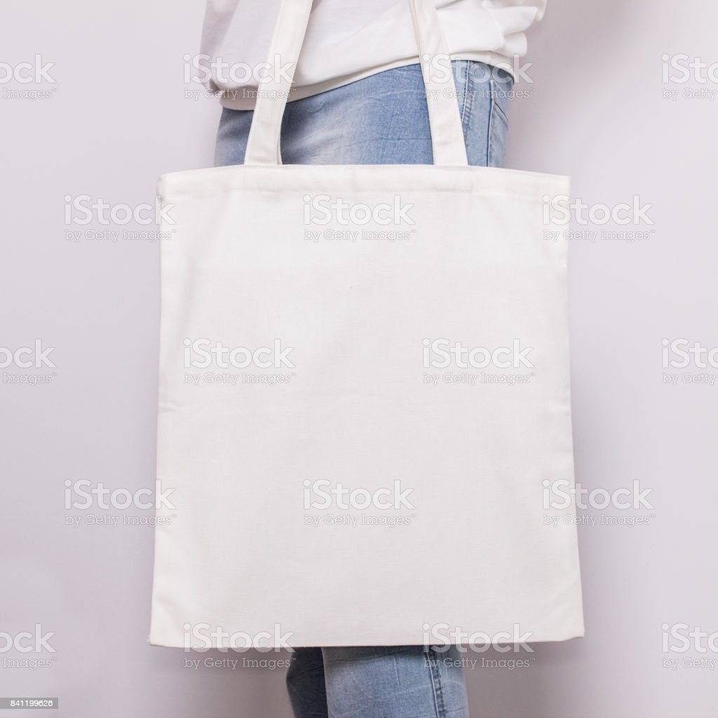 Girl in blue jeans holds blank cotton eco tote bag, design mockup. Handmade shopping bag for girls - foto stock