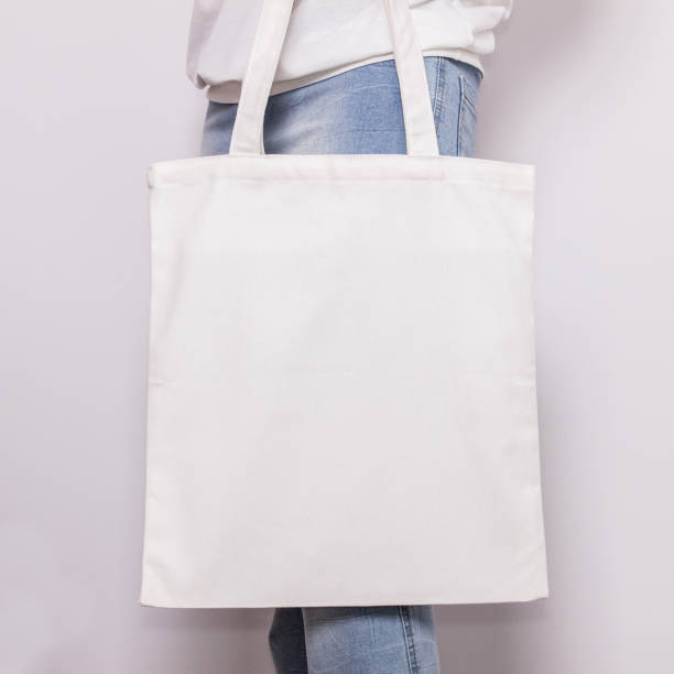 Girl in blue jeans holds blank cotton eco tote bag, design mockup. Handmade shopping bag for girls stock photo