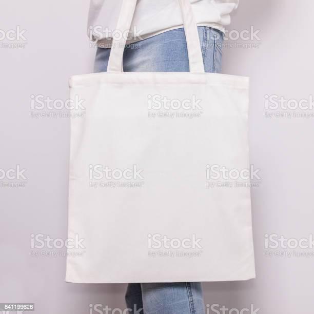 Girl in blue jeans holds blank cotton eco tote bag, design mockup. Handmade shopping bag for girls.