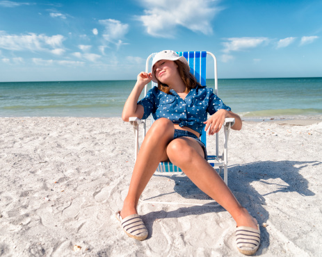 Girl in blue relaxing on the beach.