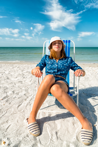 Girl in blue relaxing on the beach, vertical.