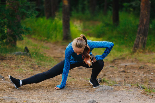 Girl in blue sportswear doing exercises outdoors in coniferous forest. Legs stretching in deep side lunge.. Healthy lifestyle sport concept. stock photo