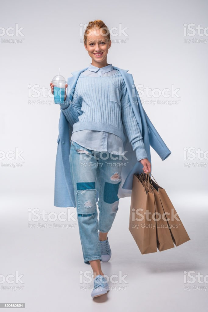 girl in blue with shopping bags stock photo