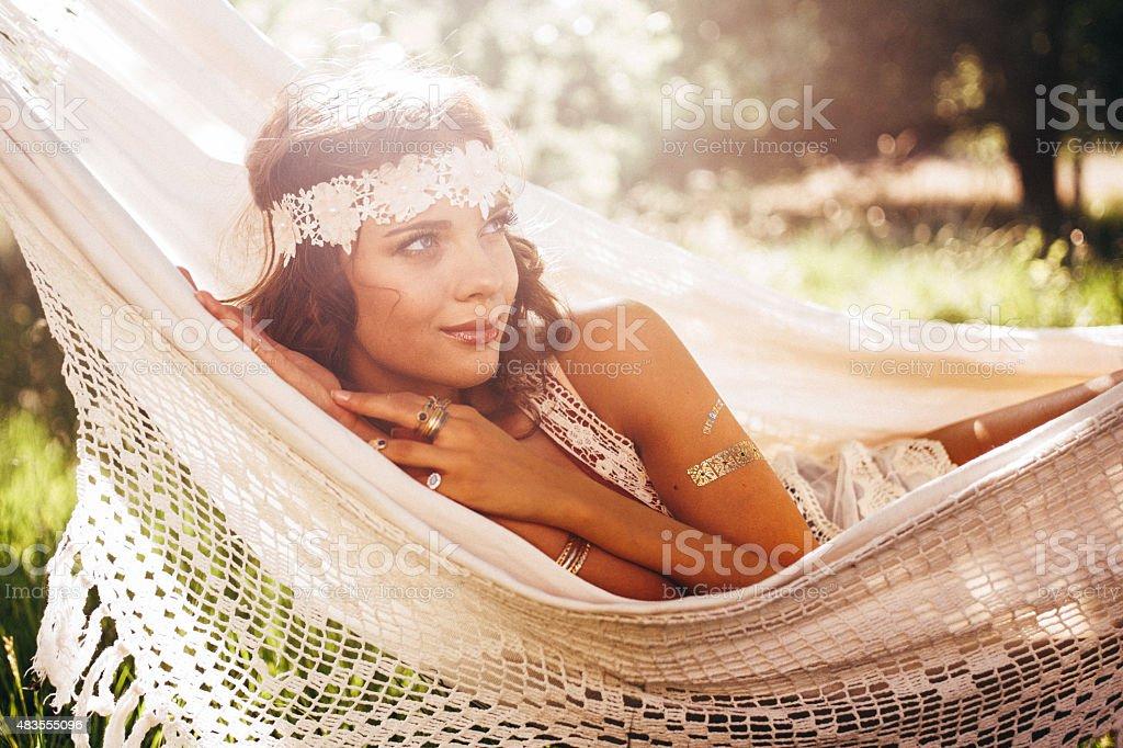 Girl in boho fashion daydreaming in a hammock in summer stock photo