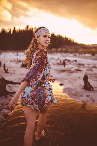mädchen in bohème-mode zu fuß über dem wasser bei sonnenuntergang - hippie kleider stock-fotos und bilder