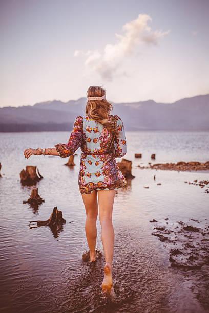 mädchen in boho-kleid mit blumenmuster und einem spaziergang über eine natürliche see - hippie kleider stock-fotos und bilder