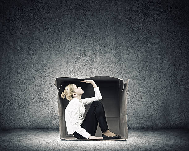 Girl in box Young businesswoman trapped in carton box trap stock pictures, royalty-free photos & images