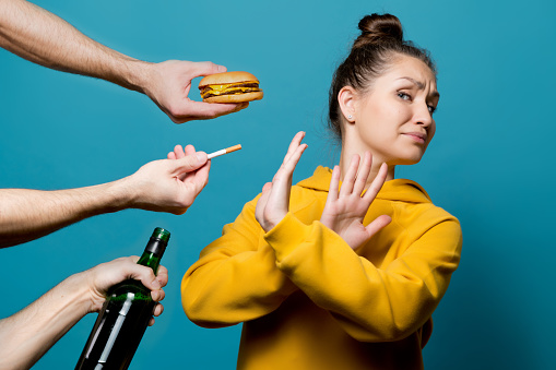 girl in bright clothes refuses junk food, alcohol and cigarettes, preferring a healthy lifestyle