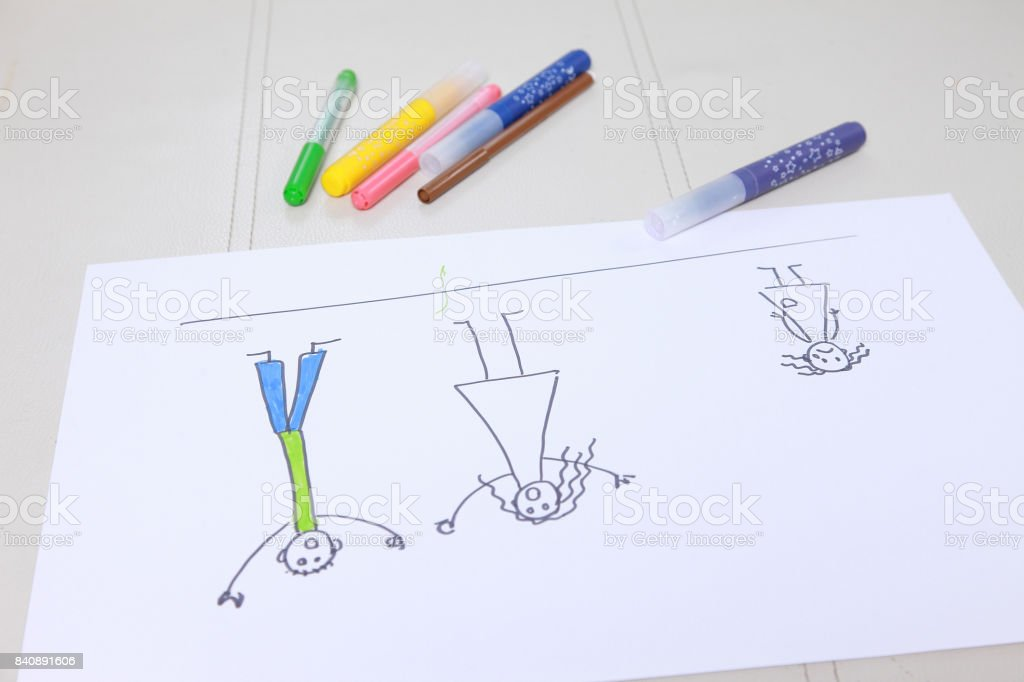 Girl in bright clothing draws a picture of the family. stock photo