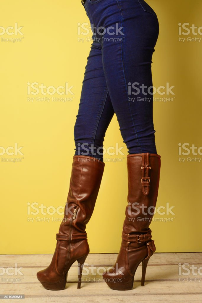 girl in brown boots and jeans stands on a white wooden floor near a yellow wall stock photo