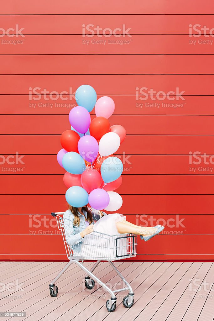 girl in cart with balloons stock photo
