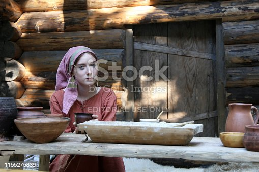 Moscow, Russia - June 2019: Girl in clothes of the early middle ages sits at a dining table near a wooden hut during the historical festival Times and epochs. Reconstruction of life in medieval Europe