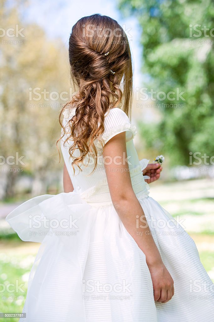 Girl in communion dress showing hairstyle. stock photo