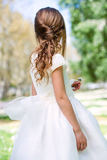 girl in communion dress showing hairstyle. - communion stock photos and pictures